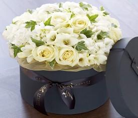 цветы фрезии и розы в шляпной коробке