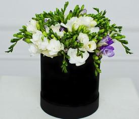 белые цветы фрезии в шляпной коробке