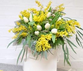 Цветы мимозы и тюльпанов в шляпной коробке